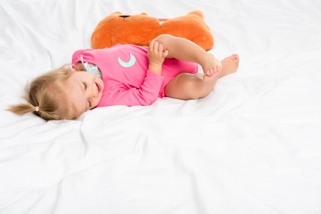 smiling baby in bodysuit with toy near by lying on bed