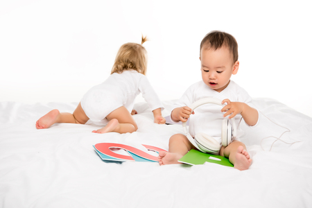 asian toddler boy holding headphones while girl crawling behind isolated on white Stock Photo