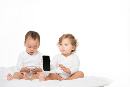 multicultural toddlers with digital smartphones isolated on white