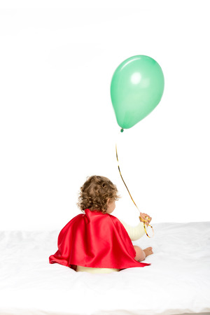 back view of adorable toddler in superhero cape holding balloon isolated on white Stock Photo