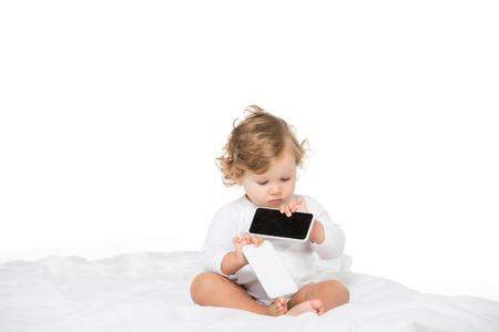 cute focused toddler holding smartphones isolated on white Stock Photo