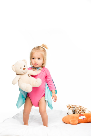 toddler girl in superhero cape holding teddy bear isolated on white Stock Photo
