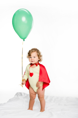 adorable toddler in superhero cape holding balloon isolated on white