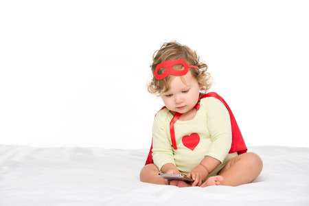 adorable toddler girl in superhero costume with smartphone isolated on white