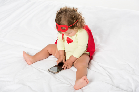 high angle view of adorable toddler girl in superhero costume with smartphone isolated on white