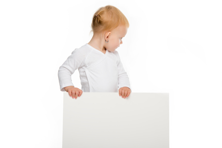 toddler girl holding blank banner in hands and looking away isolated on white