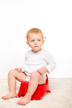 adorable baby in bodysuit sitting on pottie isolated on white Stock Photo