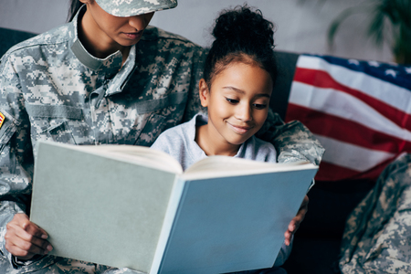 african american daughter and mother in military uniform reading book together at home