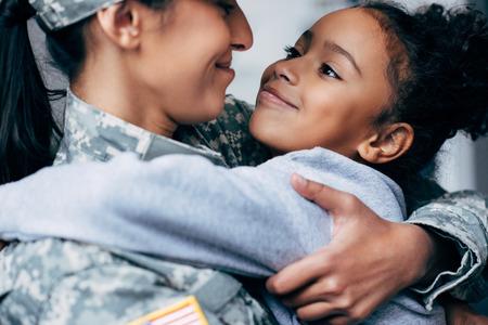 glückliche afroamerikanische Tochter, die Mutter in der Militäruniform zu Hause umarmt Standard-Bild