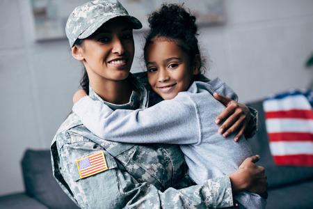 lachende Afro-Amerikaanse dochter knuffelen moeder in militair uniform thuis Stockfoto
