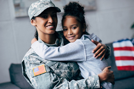 sorridente figlia afro-americana che abbraccia la madre in uniforme militare a casa Archivio Fotografico