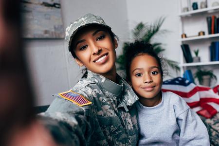 sorridente figlia afroamericana e soldato in uniforme militare prendendo selfie a casa