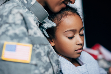cropped view african american daughter sleeping with soldier in military uniform at home