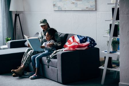 african american daughter and soldier in military uniform reading book together at home with usa flag Imagens