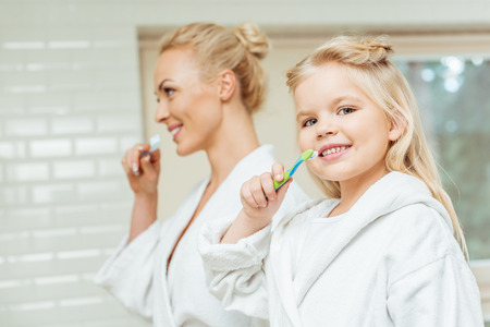 beautiful happy mother and daughter in bathrobes brushing teeth together