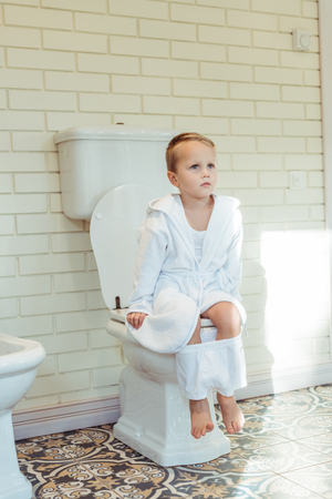 cute little boy in white underwear sitting on toilet and looking away