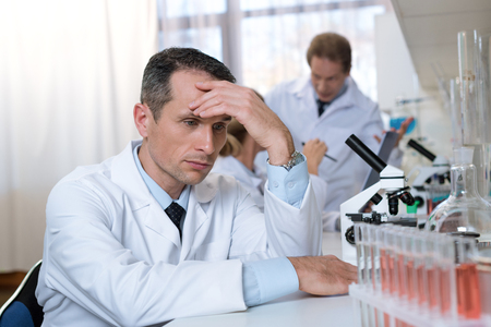 Stressed scientist sitting in laboratory during work, with hand on forehead