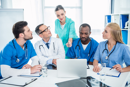 concentrated multiethnic team of doctors brainstorming and using laptop