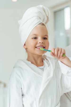 beautiful happy little girl in bathrobe and towel on head brushing teeth