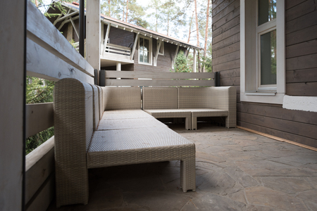 modern wicker furniture on terrace in country house