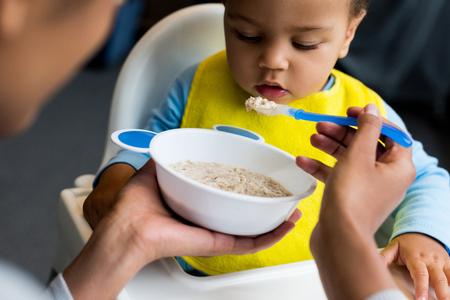 african american mother feeding little son with porridge at home Standard-Bild