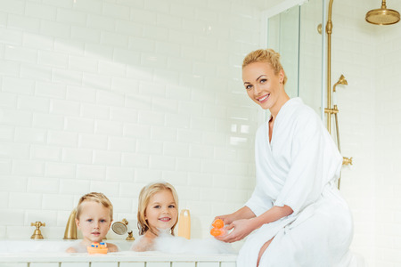 happy mother and cute little kids smiling at camera in bathroom Stock Photo