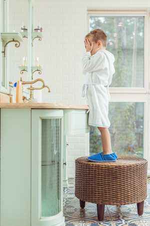 side view of cute little boy in bathrobe closing eyes with hands while standing in bathroom
