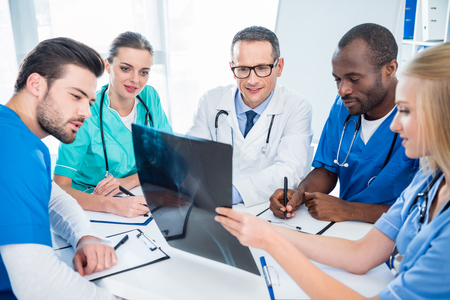 happy multiethnic team of doctors discussing x-ray scan of human pelvis