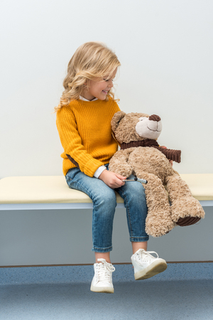 adorable little girl doing neurology examination of teddy bear Banco de Imagens