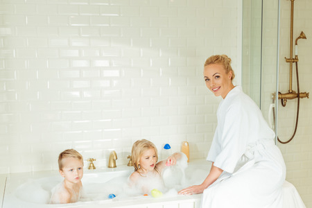 beautiful mother in bathrobe smiling at camera while washing kids in bathtub Archivio Fotografico