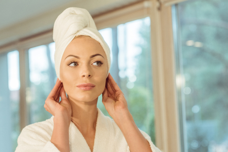 beautiful young woman with towel on head and bathrobe looking away 版權商用圖片