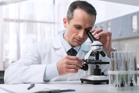 Focused male scientist in white coat doing a microscope sample analysis in chemical lab