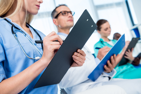 cropped shot of nurse writing in clipboard on conversation Stock Photo