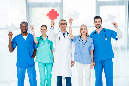 multiethnic team of doctors holding large puzzle pieces Stock Photo