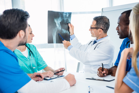 multiethnic team of doctors looking at x-ray scan of pelvis Stock Photo