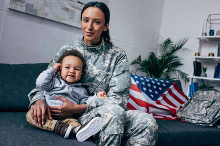 african american mother in military uniform with baby boy at home, with american flag on background Stock Photo