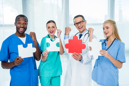 multiethnic team of doctors holding large puzzle pieces and celebrating victory