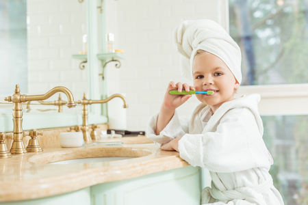 adorable little girl in bathrobe and towel brushing teeth and looking at camera 스톡 콘텐츠