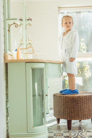 full length view of cute little boy in bathrobe looking at camera while standing in bathroom