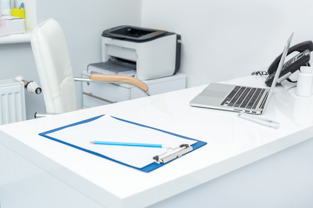 pediatrician workplace with laptop and clipboard at modern clinic Stock Photo - 102647455
