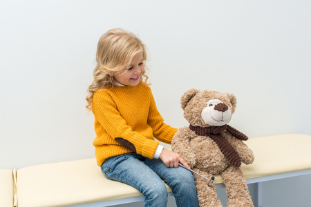 adorable little girl doing neurology examination of teddy bear while sitting on sofa