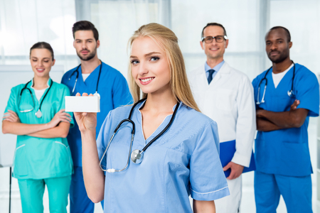 young beautiful nurse holding box of pills with colleagues standing together on background