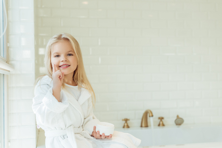 beautiful little girl in bathrobe applying face cream and smiling at camera