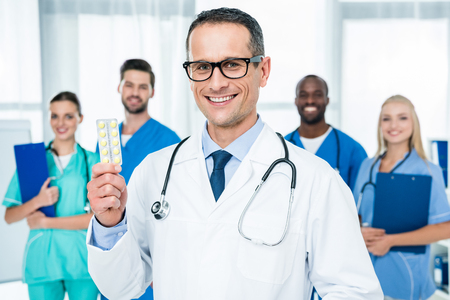 handsome mature doctor holding pills with colleagues standing together on background
