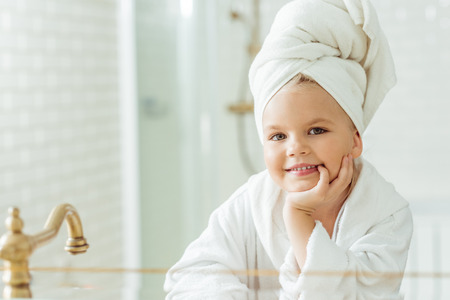 adorable little girl in bathrobe and towel on head smiling at camera in bathroom