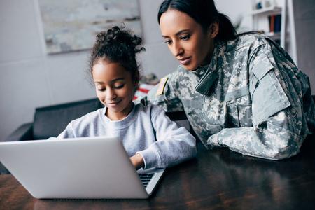 Madre afroamericana en uniforme militar e hija con portátil en casa