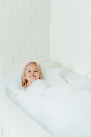 cute happy little girl sitting in bathtub with foam