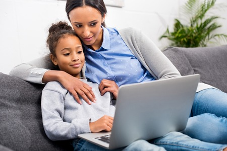 african american mother and daughter using laptop at home Stock Photo