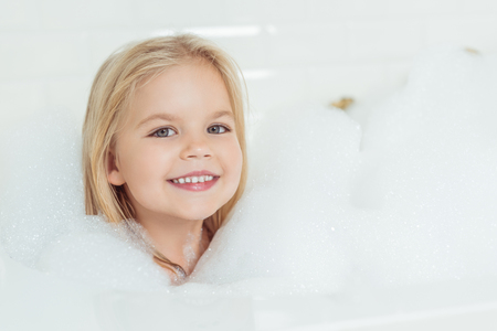beautiful little girl smiling at camera while sitting in bathtub with foam