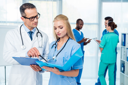 general practicioner and nurse discussing work at clinic wih colleagues standing on background Stock Photo